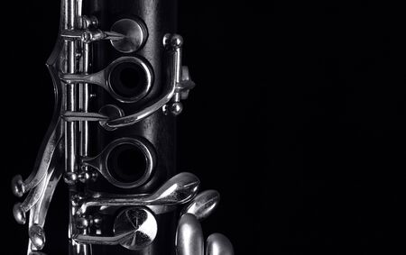 part of the old clarinet body, with the silver mechanisms on the wood. Black background and free space for text 免版税图像