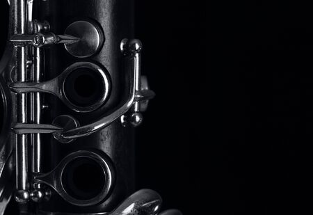 part of the old clarinet body, with the silver mechanisms on the wood. Black background and free space for text Banco de Imagens