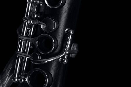 part of the clarinet body, with the silver mechanisms on the wood. Black background and free space for text Banco de Imagens