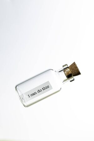 glass bottle with a message inside  and cork tap on a white background 免版税图像