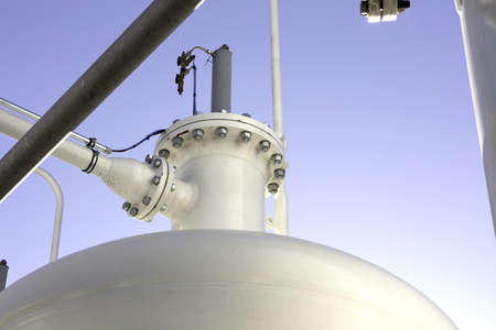 industrial background with pipes, joints, bolts and pressure tank color white with blue sky as background