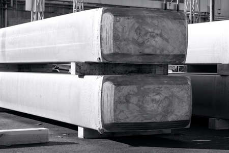 big aluminum ingots stacked in a yard foundry, raw material to be processed in a hot mill. Photo in black and white with bluish tone