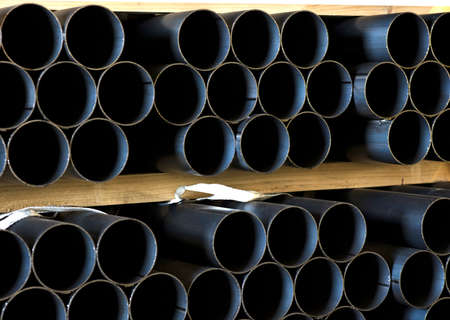 pipes of iron stacked in the warehouse on large wood pieces