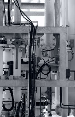 industrial background with pipes, joints, bolts, valves and electrical wires, black and white photo
