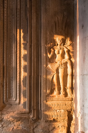 Side lit bas-relief of a woman in Angkor in Cambodia. 스톡 콘텐츠