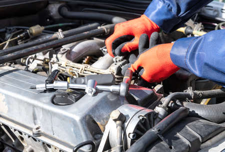 Repair, engine, screw on, workshop red gloves, screwdriver and tensioner.