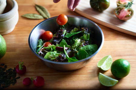 A hand throws a cherry tomato to a salad into a metal bowl on a wooden table in a kitchen. In the gastronomic photography you can see radishes, seeds, cutting board, tomatoes and lime. Stock fotó