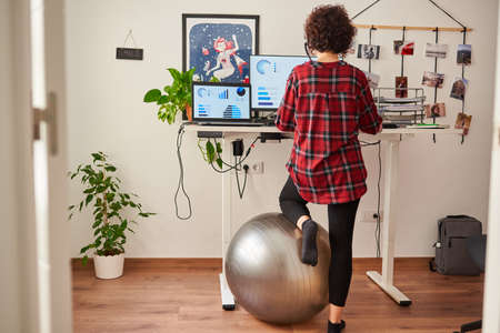 Woman working standing from home with an adjustable height desk