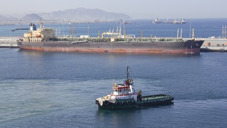 One small boat docked to oil tanker in port of Fujairah (United Arab Emirates) Stock Photo