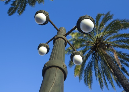 street light and palm on the seafront of Sitges, Barcelona (Spain)