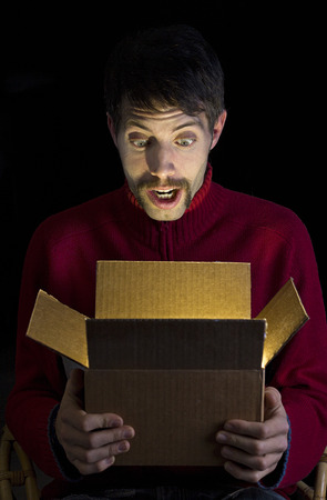 man opening box with surprised face