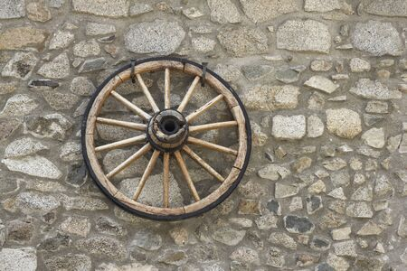 stone wall background with old wooden chariot wheel Stock Photo