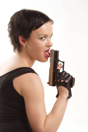 Stylish brunette girl in black clothes licking her gun photo