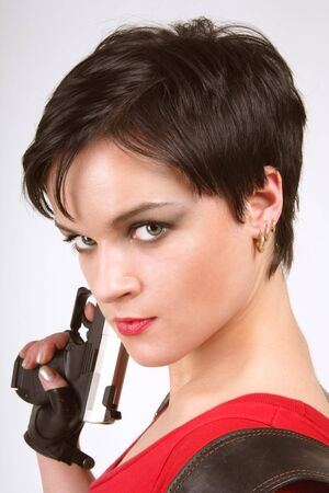Beautiful dark-haired girl in leather gloves with pistol and pistol holster photo