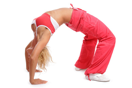 athletic gear: Athletic tanned girl in red sportive gear making a bridge Stock Photo