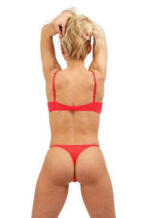 Blonde sportive girl in sexy red lingerie stands with hands up and her back turned toward us