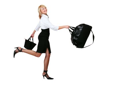 Nice blond smiling girl in white shirt and black skirt running with bags in her hands Stock Photo