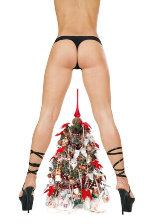 Beautiful woman's bottom and legs in black hyper-sexy stilettos and decorated New Year tree Stock Photo - 2105001