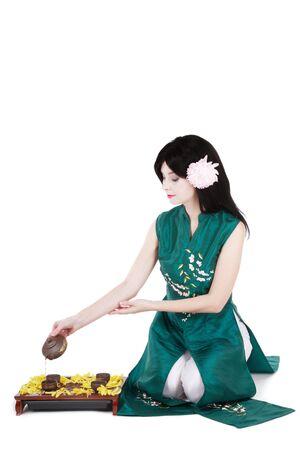informal clothing: Brunette in green asian costume arranging tea ceremony