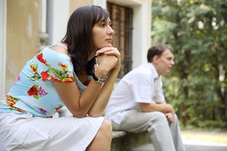 Young sad woman and man sitting on marble steps in park, selective focus photo