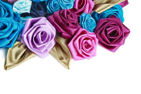 Blue, vinous, pink and turquois handmade silk roses on white background with copy space below photo