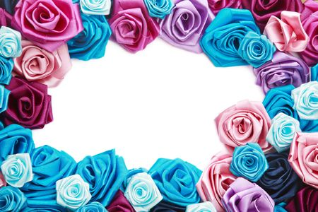 Valentines frame of blue, vinous, pink and turquois handmade silk roses on white background with copy space in center photo