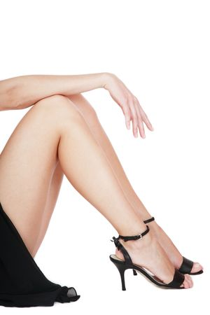 Long beautiful legs of woman in black dress sitting on white background put her hand on knees photo