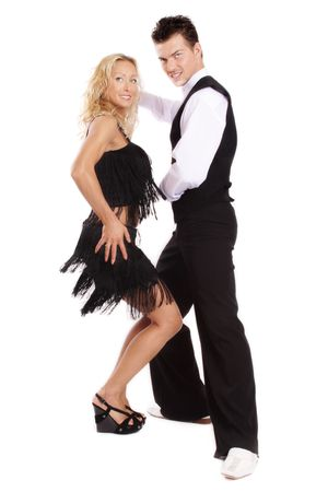 Beautiful blond and brunet dancing salsa on white background