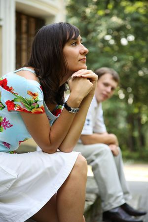 Young woman and man sitting on marble steps in park, selective focus