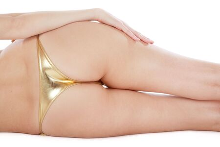 Pretty bum of slim girl in golden bikini lying on white background Stock Photo - 2598928