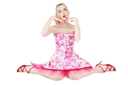 looking upwards: Beautiful blond girl in stylish pink dress sitting on white background and looking upwards with thoughtful expression