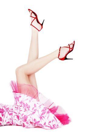Legs of woman in red stilettos and pink dress lying on white background