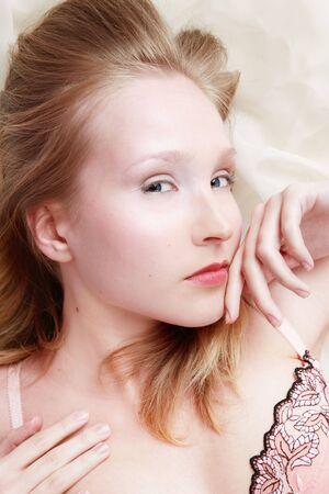 Beautiful sensual blond girl with clear makeup lying on silk drape photo