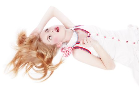 careless: Beautiful blond girl lying on white background with lollipop in her hand and looking upwards Stock Photo