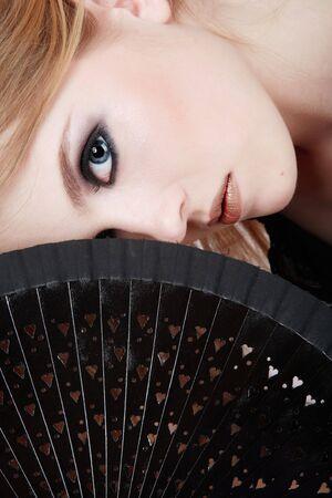 Portrait of beautiful blond girl with black fan photo