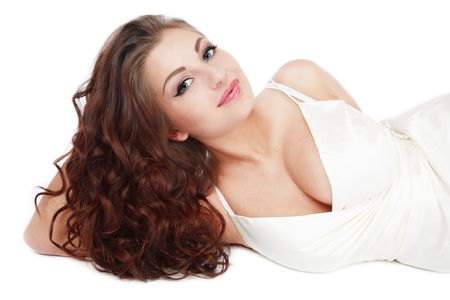 permanent wave: Beautiful tanned smiling girl with gorgeous curling hair lying on white background