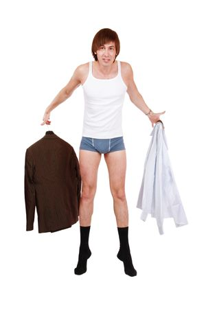Young man in underwear and socks holding suit an shirt with confused expression