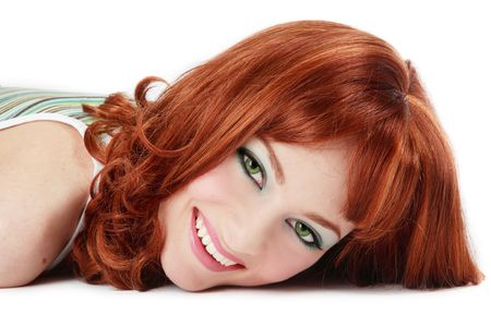 lighthearted: Beautiful red-haired girl with green eyes lying on white background and laughing
