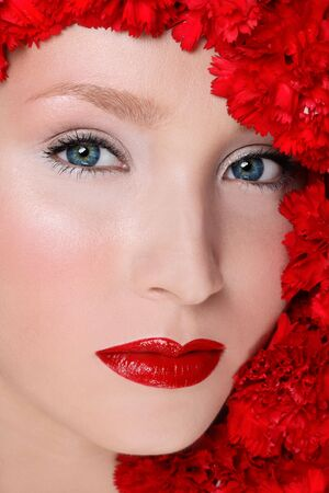 Close-up portrait of beautiful woman with red lipstick over red flowers photo