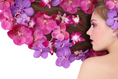 Beautiful girl lying on white background with orchids in her long hair photo