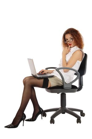 Pretty slim young girl in stockings and stilettos sitting on office chair with notebook photo