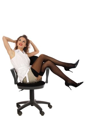 Pretty slim young girl in stockings and stilettos sitting on office chair Stock Photo