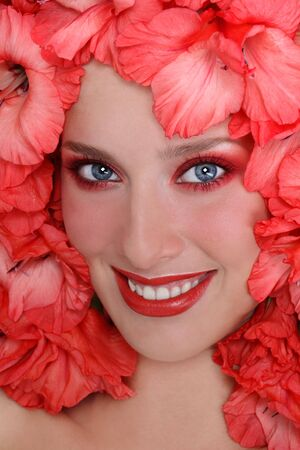 Portrait of beautiful young smiling girl with bright makeup in coral cornflags photo