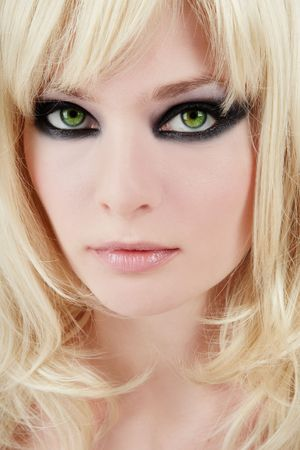 Close-up portrait of young green-eyed blonde with trendy makeup