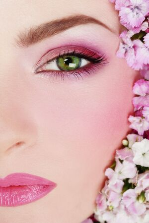 allure: Close-up shot of beauiful womans face with bright makeup