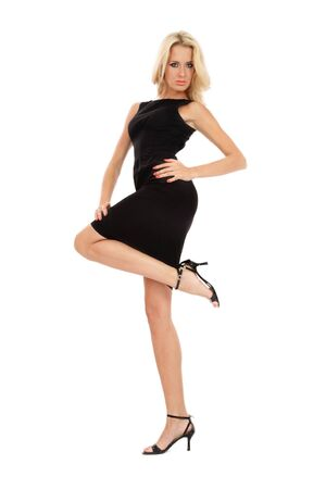 Beautiful slim blonde girl in black cocktail dress standing on white background  photo