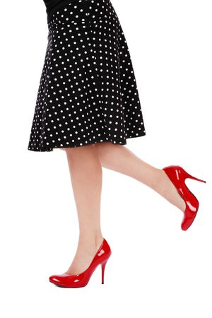 Legs of woman in red stilettos and black polka dot skirt photo