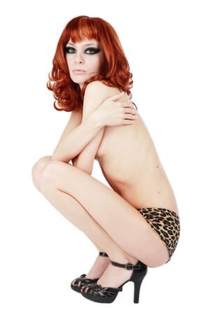 Beautiful slim red-headed girl in panties with leopard print and black stilettos sitting on white background photo
