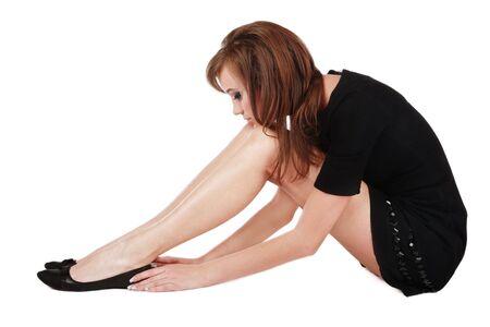 esitazione: Slim ragazza con le gambe lunghe conciate seduta su sfondo bianco