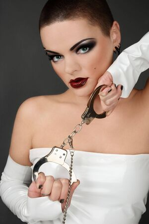 beautiful bdsm: Girl in white vinyl dress and gloves holding cuffs Stock Photo